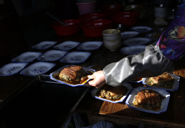 A local cook prepares a traditional ethnic Tujia wedding feast for about 2000 guests during celebrations marking the Lunar New Year, in Ziqiu town, Changyang county of China's Hubei province, February 15, 2016. (Photo by Jason Lee/Reuters)