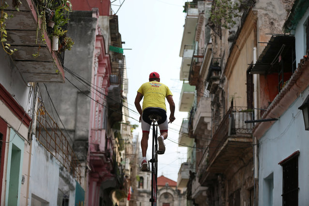 Felix Guirola, 52, rides a homemade bike with an advertising banner in Havana, Cuba, July 20, 2016. (Photo by Alexandre Meneghini/Reuters)