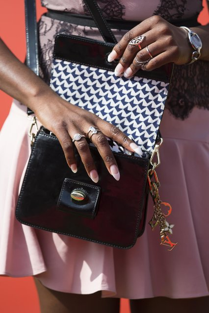A spectator reaches into her handbag during Aintree race meeting's Ladies Day the day before the Grand National horse race at Aintree Racecourse Liverpool, England, Friday, April 10, 2015. (Photo by Jon Super/AP Photo)