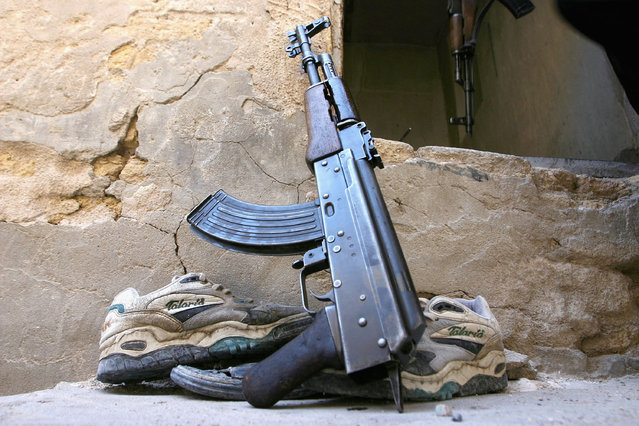 An AK-47 rifle is laid against the wall of a make shift militia mosque on August 20, 2004 in Najaf. (Photo by Ghaith Abdul-Ahad/Getty Images)
