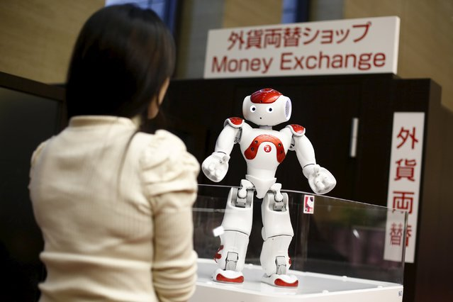 "A woman interacts with a ""Nao"" humanoid robot, by Aldebaran Robotics that offers basic service information, during a presentation at a branch of the Bank of Tokyo-Mitsubishi UFJ (MUFG) in Tokyo April 13, 2015. (Photo by Thomas Peter/Reuters)"