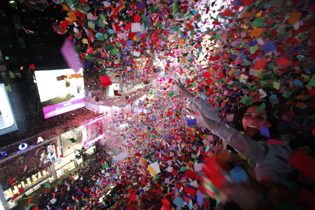 Confetti is dropped on revelers at midnight during New Year's Eve celebrations in Times Square in New York January 1, 2014. (Photo by Gary Hershorn/Reuters)