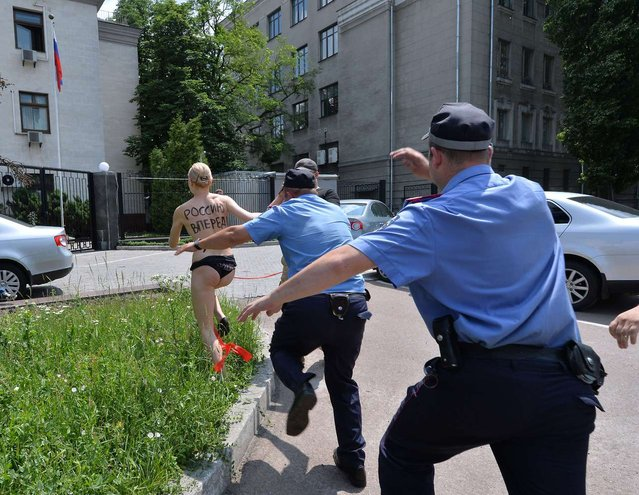 "A «FEMEN» feminist tries to evade arrest in Kiev after she shouted ""Vladimir, I love you!"" and performed an impersonation of Russian rhythmic gymnast Alina Kabayeva with a ribbon, on June 7, 2013. Russian President Vladmir Putin, who announced his divorce this week, has previously been romantically linked with Kabayeva, an Olympian turned legislator 31 years his junior. (Photo by Sergei Supinsky/AFP Photo)"