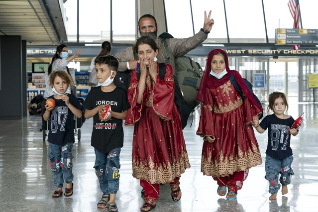 Families evacuated from Kabul, Afghanistan, walk through the terminal before boarding a bus after they arrived at Washington Dulles International Airport, in Chantilly, Va., on Friday, August 27, 2021. (Photo by Jose Luis Magana/AP Photo)