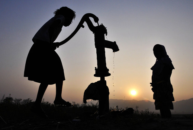 Indian children collect drinking water from a tube-well in the village of Murkata in Morigoan district, some 70 kms from Guwahati on December 30, 2013. With an annual monsoon, India does not lack water, but it struggles to preserve water due to poor storage and distribution systems. (Photo by Biju Boro/AFP Photo)
