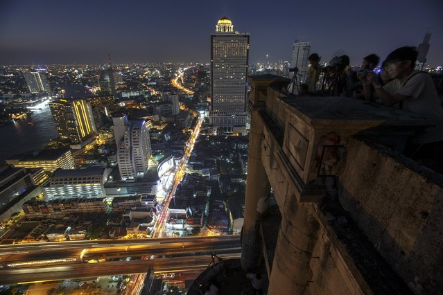 Visitors take photographs from a top of an abandoned skyscraper in Bangkok April 19, 2015. (Photo by Athit Perawongmetha/Reuters)