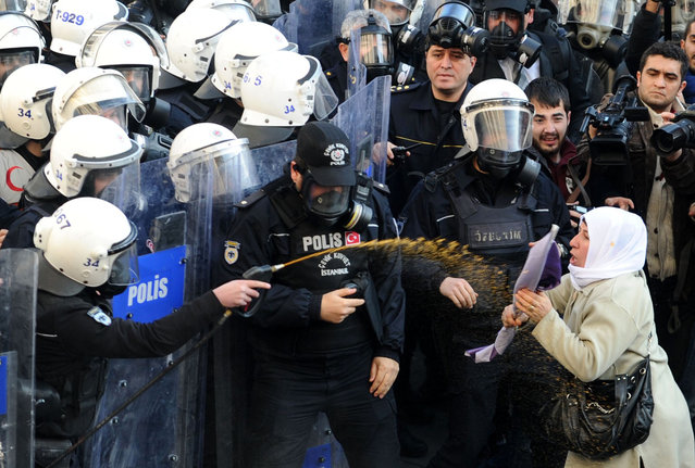 A woman (R) confronts Turkish riot policemen as they spray tear gas on demonstrators trying to march on January 9, 2014, in Istanbul, to the French consulate demanding justice for three female Kurdish rebels killed a year ago in Paris. Between 500 to 600 Kurdish protesters had gathered in front of Istanbul's Galatasaray High School, shouting (Photo by Ozan Kose/AFP Photo)