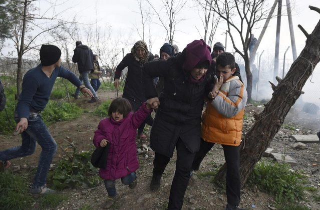 A woman holds her children on the Greek side of the border as they run away after Macedonian police fired tear gas at a group of the refugees and migrants who tried to push their way into Macedonia, breaking down a border gate near the northern Greek village of Idomeni on Monday, February 29, 2016. No arrests or injuries were reported. About 6,500 migrants are stuck on the Greek-Macedonian border at Idomeni, waiting to travel north, but Macedonia is only admitting a trickle. (Photo by Giannis Papanikos/AP Photo)