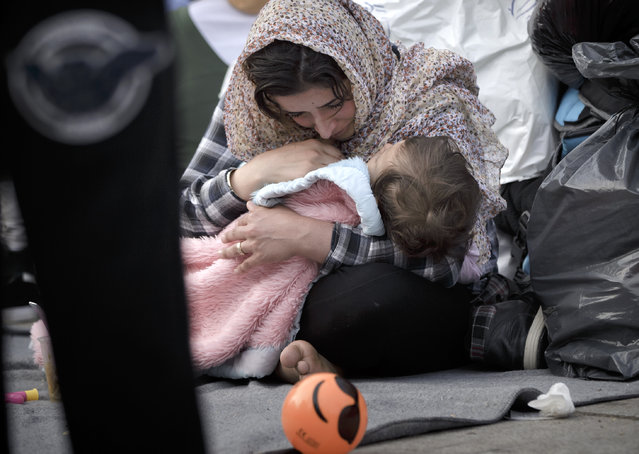 A migrant woman cries while holding a baby, in Athens, Monday, February 29, 2016, at the Victoria Square, where most newly-landed migrants head after reaching the Greek capital from the Aegean Sea islands. (Photo by Vadim Ghirda/AP Photo)