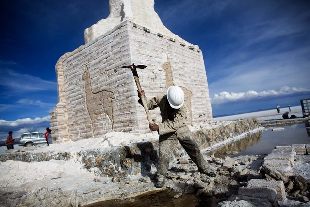 A worker makes a hole in the salt to fill it with water at a monument made of salt to welcome the Dakar Rally at the Uyuni Salt Flats. (Photo by Victor R. Caivano/Associated Press)