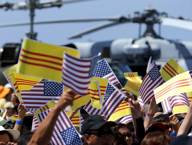 Visiting members of the Vietnamese community wave U.S. flags and the flag of former South Vietnam as they attend a ceremony on the flight deck of the USS Midway as the ship commemorates the 40th Anniversary of Operation Frequent Wind and the fall of Saigon in San Diego, California, United States April 26, 2015. (Photo by Mike Blake/Reuters)