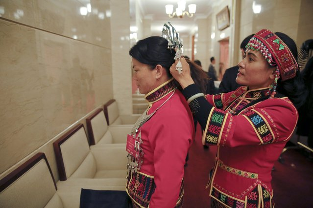 Ethnic Minority delegates adjust headwear as they attend Hainan delegation group discussion at the National People's Congress (NPC) at the Great Hall of the People in Beijing, China March 7, 2016. (Photo by Damir Sagolj/Reuters)