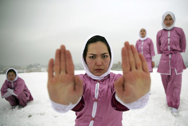 Shaolin martial arts students practice on a hilltop in Kabul, Afghanistan, Tuesday, January 25, 2017. Teacher Sima Azimi, 20, not pictured, who is originally from Jaghuri in central Afghanistan, trains nine students in the martial arts to prepare for Olympic competitions, but also to protect themselves on the streets of Kabul, where women are routinely harassed. (Photo by Massoud Hossaini/AP Photos)