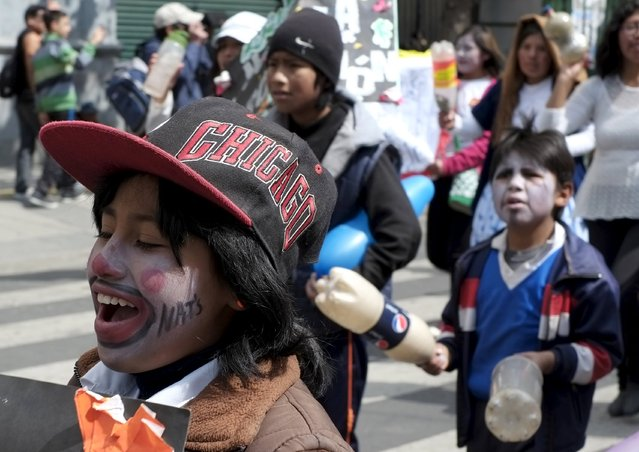 Bolivian children participate in a rally commemorating International Workers' Day in La Paz May 1, 2015. Bolivian children are allowed to work from the age of 10, according to a law enacted in July 2014, according to local media. International Workers' Day, also known as Labour Day or May Day, commemorates the struggle of workers in industrialised countries in the 19th century for better working conditions. (Photo by David Mercado/Reuters)
