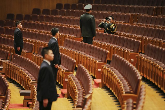 A military officer has his picture taken as security agents stand guard after the closing ceremony of the Chinese People's Political Consultative Conference (CPPCC) at the Great Hall of the People in Beijing, China, March 14, 2016. (Photo by Damir Sagolj/Reuters)