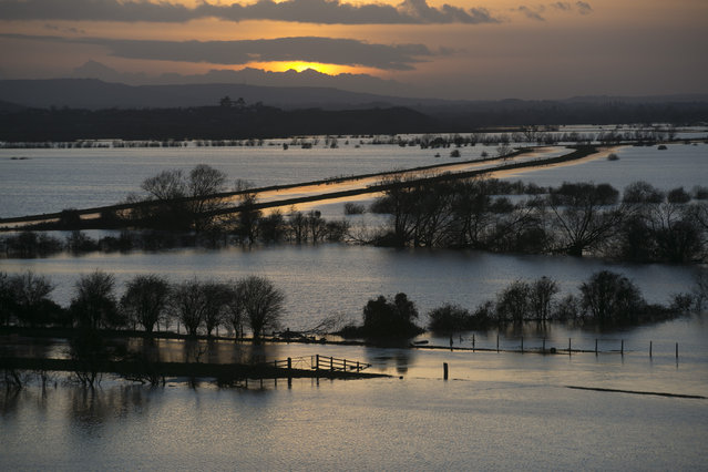 The sun sets over flooded fields surrounding the River Tone that has burst its banks on the Somerset Levels viewed from Windmill Hill, in Stoke-St-Gregory on February 2, 2014 near Langport in Somerset, England. With high tides, combined with gale force winds and further heavy rain, some parts of the UK are bracing themselves for more flooding.  (Photo by Matt Cardy/Getty Images)