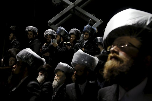 Ultra-Orthodox Jewish men take part in the wedding ceremony of the grandson of Rabbi Yosef Dov Moshe Halberstam, religious leader of the Sanz Hasidic dynasty and the granddaughter of the religious leader of Toldos Avraham Yitzchak Hasidic dynasty, in Netanya, Israel, March 15, 2016. (Photo by Baz Ratner/Reuters)