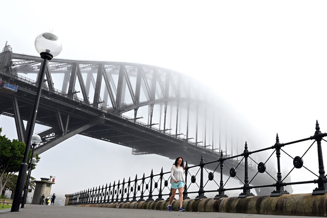 People walk under Australia's iconic landmark Harbour Bridge in Sydney on April 3, 2019, as heavy fog blankets the city. Low visibility due to heavy fog affected traffic in the city and caused flight delays at the Sydney airport. (Photo by Saeed Khan/AFP Photo)