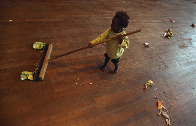 A child plays with a broom at a shelter for victims of immigrant attacks in Johannesburg, Wednesday, April 22, 2015. (Photo by Denis Farrell/AP Photo)