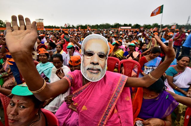 A woman wearing a mask of Prime Minister Narendra Modi dances as she attends an election campaign rally being addressed by Bharatiya Janata Party (BJP) President Amit Shah at Ahatguri village in Morigaon district in the northeastern state of Assam, April 5, 2019. (Photo by Anuwar Hazarika/Reuters)