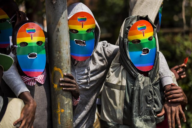 "Men wear masks during a rare public protest against Uganda's increasingly tough stance against homosexuality outside the Uganda High Commission in Nairobi, Kenya, on February 10, 2014. Homosexuality has been criminalized in the country where lawmakers have recently passed a new bill that calls for life imprisonment for ""aggravated"" homosexual acts. (Photo by Ben Curtis/Associated Press)"