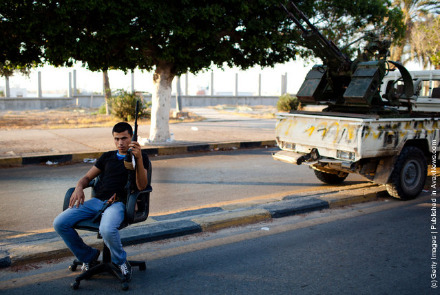 A Libyan Rebel fighter sits at a check point