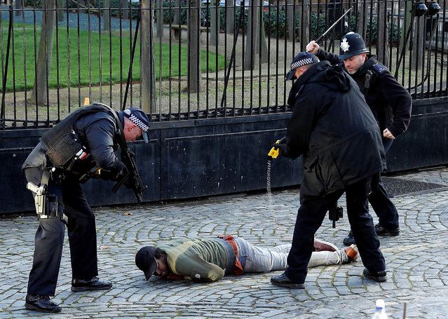 Armed police Taser a man inside the grounds of the Houses of Parliament on 11 December 2018. (Photo by Peter Nicholls/Reuters)