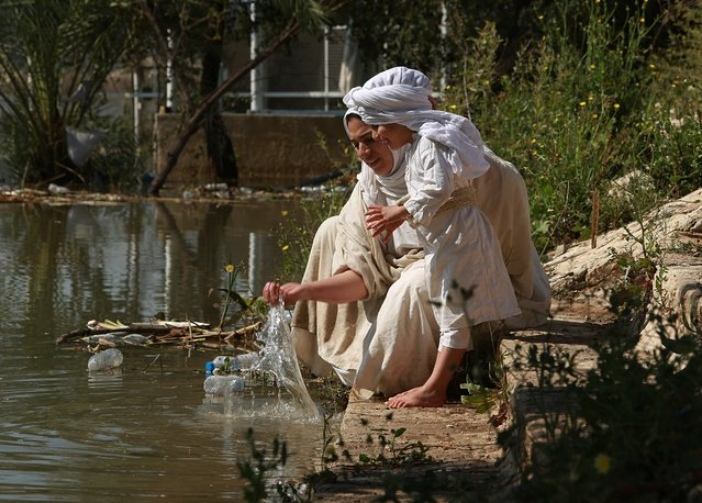 """Followers of the Sabean Mandaeans, a pre-Christian sect that follows the teachings of John the Baptist, perform their rituals alongside the Tigris river during a celebration marking """"Banja"""" or Creation Feast in central Baghdad, Iraq, Friday, March 15, 2019. Iraqi Sabaean Mandeans view the Bible's John the Baptist as savior and submerge themselves in the Tigris in an annual five-day ritual. (Photo by Hadi Mizban/AP Photo)"""