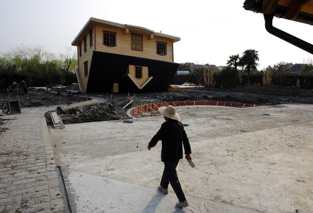 A female labourer walks next to an upside-down house under construction at Fengjing Ancient Town, Jinshan District, south of Shanghai, March 17, 2014. (Photo by Carlos Barria/Reuters)