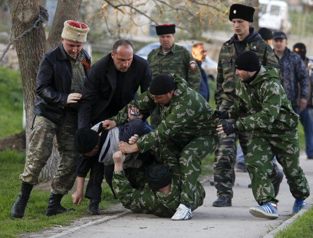 Members of pro-Russian self-defence units block and detain an unidentified man outside a military airbase in the Crimean town of Belbek near Sevastopol March 22, 2014. (Photo by Vasily Fedosenko/Reuters)