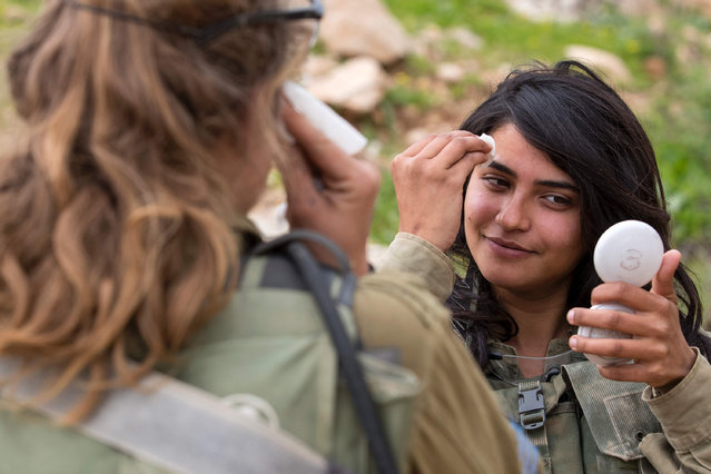 Israeli soldiers from the mixed-gender Lions of the Jordan battalion, under the Kfir Brigade, clean their face after taking part in a last training before being assigned their posting, on February 28, 2017, near the West Bank village of Bardale, east of Jenin. (Photo by Jack Guez/AFP Photo)