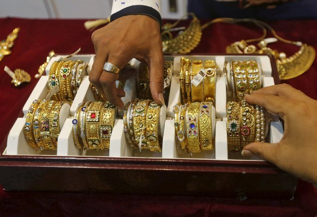 A salesman helps a customer (R) to select gold bangles at a jewelry showroom in Mumbai, India, May 21, 2015. As India meets most of its gold requirements through imports, dwindling local purchases during what should typically be the peak season will dent global prices of the metal, with a looming hike in U.S. interest rates and slower demand from No.2 consumer China further adding to the gloom. (Photo by Shailesh Andrade/Reuters)