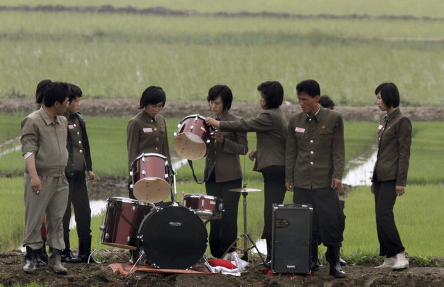 Members of a music group check a drum on a path amid fields as they pack up their instruments after giving a performance to greet the farmers at Hwanggumpyong Island, near the North Korean town of Sinuiju and the Chinese border city of Dandong June 6, 2012. (Photo by Jacky Chen/Reuters)