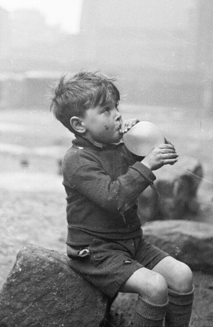 A young boy blowing up a balloon in the Gorbals area of Glasgow on January 31, 1948. (Photo by Bert Hardy/Picture Post/Getty Images)