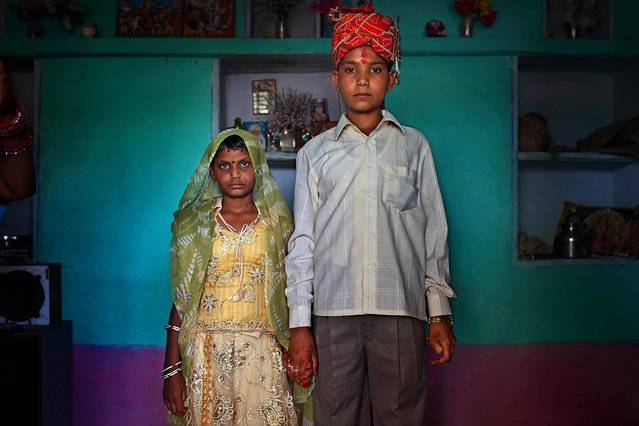 Maya, 8, and Kishore, 13, pose for a wedding photo inside their new home, the day after the Hindu holy day of Akshaya Tritiya, called Akha Teej in North India. Despite legislation forbidding child marriage in India (Child Marriage Restraint Act-1929) and the much more progressive Prohibition of Child Marriage Act (2006) and many initiatives to prevent child marriage, marrying children off at a very tender age continues to be accepted by large sections of society. (Photo by Stephanie Sinclair/VII Photo Agency)