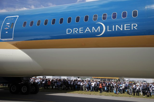 Onlookers gather as the Boeing 787 Dreamliner waits on the tarmac for its demonstration flight of the Paris Air Show,  in Le Bourget airport, north of Paris, Tuesday, June 16, 2015. Some 300,000 aviation professionals and spectators are expected at this weekends Paris Air Show, coming from around the world to make business deals and see dramatic displays of aeronautic prowess and the latest air and space technology. (AP Photo/Francois Mori)