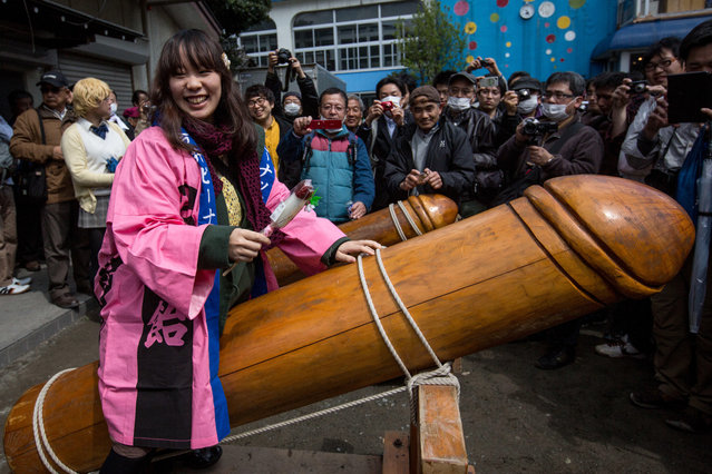 A woman poses for photographers as she sits on a large wooden phallic sculpture during Kanamara Matsuri (Festival of the Steel Phallus) on April 6, 2014 in Kawasaki, Japan. The Kanamara Festival is held annually on the first Sunday of April. The pen*s is the central theme of the festival, focused at the local pen*s-venerating shrine which was once frequented by prostitutes who came to pray for business prosperity and protection against sexually transmitted diseases. (Photo by Chris McGrath/Getty Images)