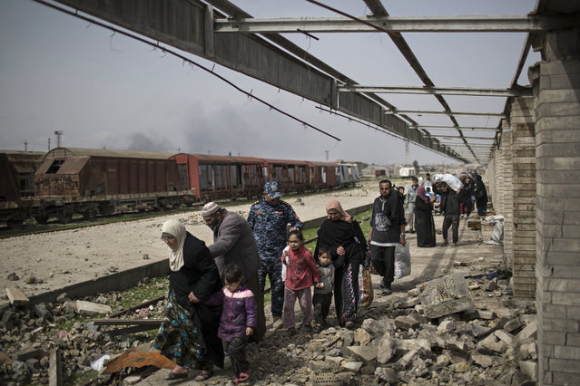 Iraqi civilians flee through a destroyed train station during fighting between Iraqi security forces and Islamic State militants, on the western side of Mosul, Iraq, Sunday, March 19, 2017. (Photo by Felipe Dana/AP Photo)