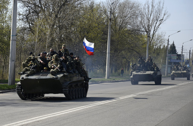 Armed men, wearing black and orange ribbons of St. George – a symbol widely associated with pro-Russian protests in Ukraine, drive an airborne combat vehicle (L) with a Russian flag seen on the top, outside Kramatorsk April 16, 2014. Ukrainian forces tightened their grip on the eastern town of Kramatorsk on Wednesday after securing control over an airfield from pro-Russian separatist militiamen, prompting Russian President Vladimir Putin to warn of the risk of civil war. (Photo by Maks Levin/Reuters)
