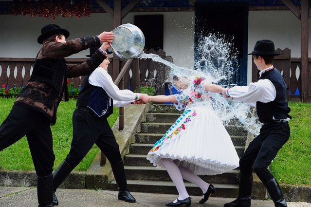 "A local school girl in traditional clothes of the ""Kalocsa"" region react as boys throw water in Kalocsa, some 100 km south of Budapest on April 17, 2014 during a rehearsal of the traditional Easter celebrations by the members of the local folk dance group. Locals from south Hungary celebrate Easter with the traditional ""watering of the girls"", a fertility ritual rooted in Hungary's tribal pre-Christian past, going as far back as the second century AD. (Photo by Attila Kisbenedek/AFP Photo)"