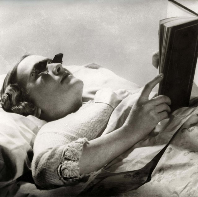 An English woman wears a pair of spectacles especially designed for reading in bed. Date: 1936. (Photo by Mary Evans Picture Library/Caters News)