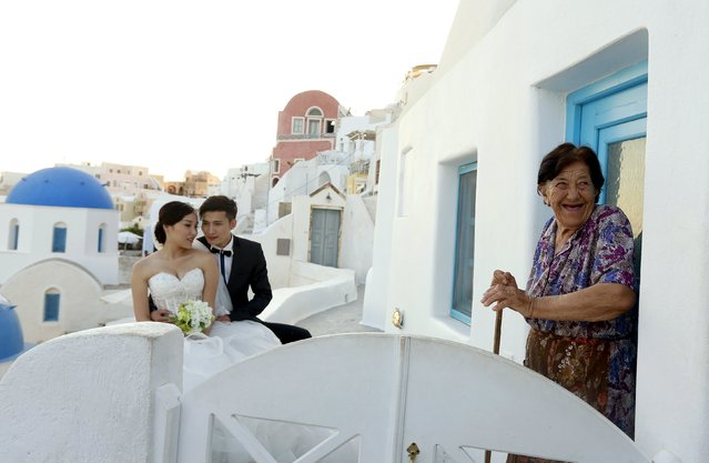 A resident reacts as a couple have their wedding picture taken on the Greek island of Santorini, Greece, July 2, 2015. The International Monetary Fund delivered a stark warning on Thursday of the huge financial hole facing Greece as angry and uncertain voters prepare for a referendum that could decide their country's future in Europe. (Photo by Cathal McNaughton/Reuters)