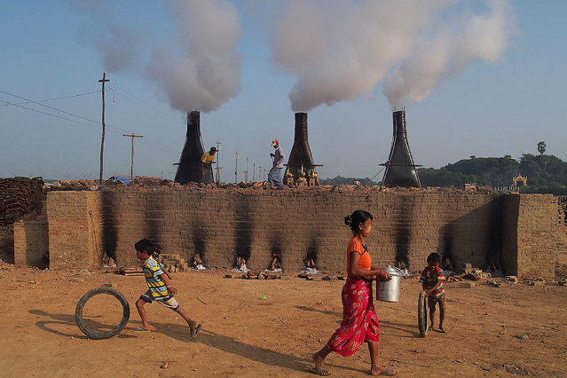 Children play in front of a brick factory on the outskirts of the northern Myanmar city of Mandalay on December 14, 2015. (Photo by Phyo Hein Kyaw/AFP Photo)