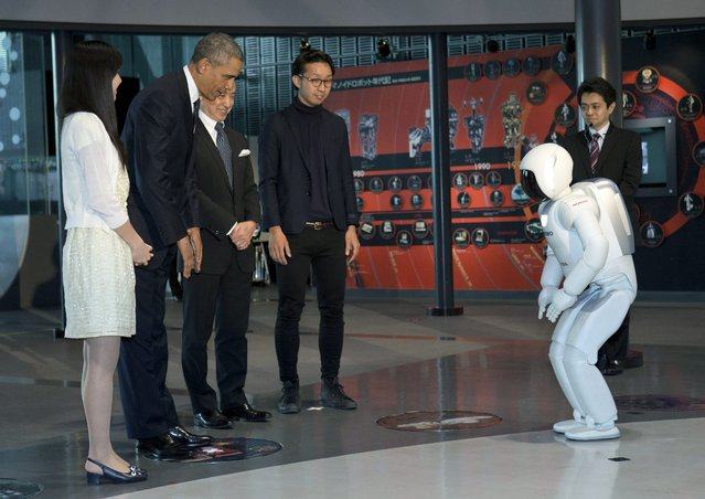 President Barack Obama and ASIMO, an acronym for Advanced Step in Innovative MObility, bow to each other during a youth science event at the National Museum of Emerging Science and Innovation, known as the Miraikan, in Tokyo, Thursday, April 24, 2014. Showing solidarity with Japan, Obama affirmed Thursday that the U.S. would be obligated to defend Tokyo in a confrontation with Beijing over a set of disputed islands, but urged all sides to resolve the long-running dispute peacefully. (Photo by Carolyn Kaster/AP Photo)