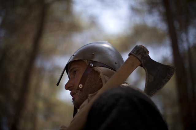 In this Saturday, July 4, 2015 photo, an Israeli member of a knight club gets ready for the reenactment of the Battle of Hattin in Lavi Forest, northern Israel. (Photo by Oded Balilty/AP Photo)