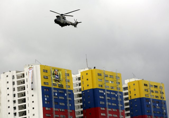 A helicopter from the Venezuelan Air Force flies past a building with the colors of the Venezuelan flag during a military parade to celebrate the anniversary of Venezuela's independence in Caracas, July 5, 2015. (Photo by Jorge Dan Lopez/Reuters)