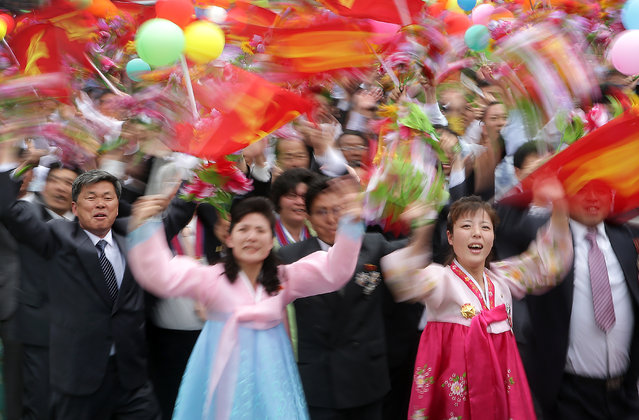 North Koreans wave flower bouquets and balloons as they march during a parade at the Kim Il Sung Square on Tuesday, May 10, 2016, in Pyongyang, North Korea. (Photo by Wong Maye-E/AP Photo)