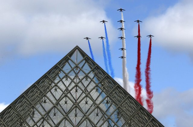Alphajets from the French Air Force Patrouille de France in the formation of a Croix de Lorraine cross and releasing trails of red, white and blue smoke, colors of French national flag, fly over the Pyramid of the Louvre Museum during the traditional Bastille day military parade in Paris, France, July 14, 2015. (Photo by Gonzalo Fuentes/Reuters)
