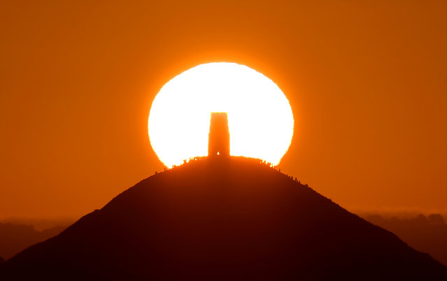 Revellers celebrate the Summer Solstice as the sun rises at Glastonbury Tor in Glastonbury, Britain, June 21, 2019. (Photo by Toby Melville/Reuters)