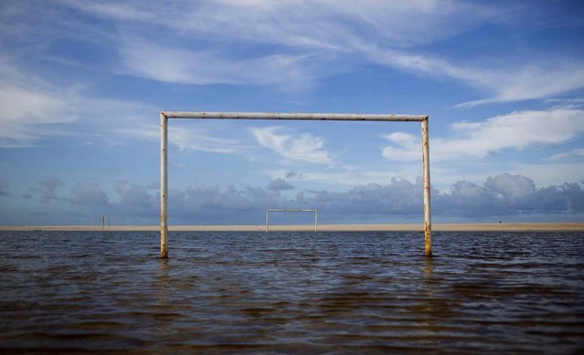 A soccer field is seen under water during a high tide in Beberibe, near Fortaleza, Brazil, on March 27, 2014. Beberibe is one of the coast cities located south-east of Fortaleza with many magnificent beaches popular with tourists. Fortaleza is one of the host cities of the 2014 soccer World Cup. (Photo by Felipe Dana/Associated Press)